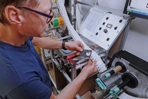 Mitarbeiter kontrolliert Etiketten-Lohndrucke
